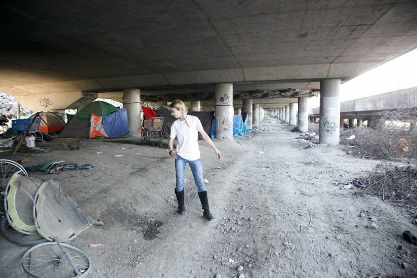 Little Ricks, 28, a resident of the Jungle homeless encampment in Seattle, searches for a bus pass that was to serve as her mode of transportation. Photo: Katy Cossette